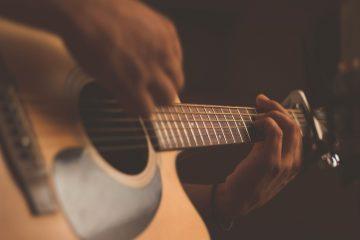 Persona tocando la guitarra para ahorrar en festivales musicales.