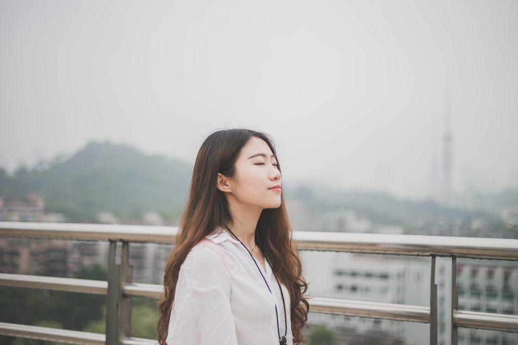 """alt=""""Mujer asiática disfrutando de la calma necesaria para invertir""""/>"""
